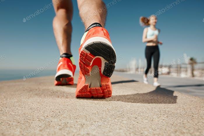 Runner feet running on road closeup on shoe. Sportsman fitness s