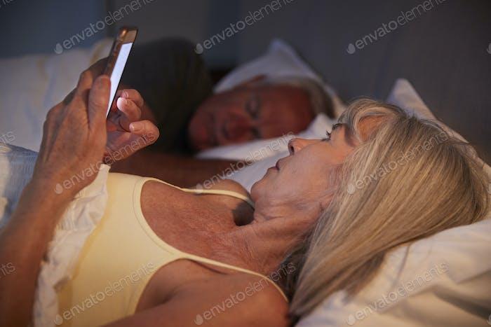 Schlaflose Senior Frau im Bett bei Nacht mit Handy