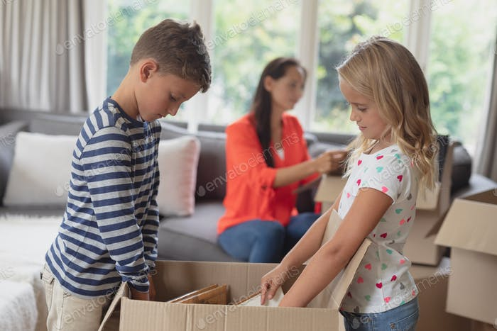 Caucasian siblings unpacking cardboard box while Caucasian mother looking a document in living room