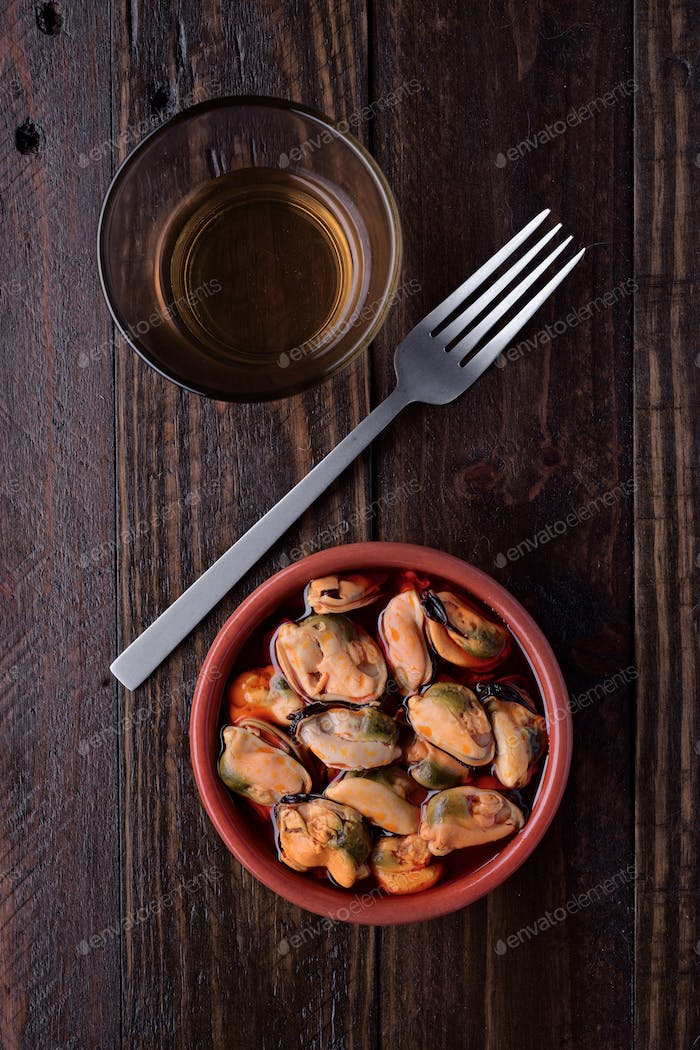 clay pot filled with mussels in sauce isolated on rustic wooden board