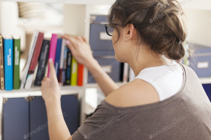 Woman choosing favourite book from home library