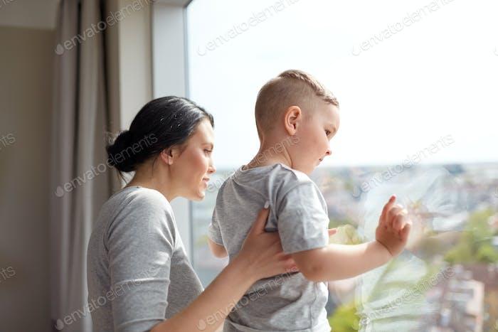 mère et fils regardant par la fenêtre à la maison