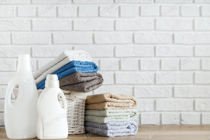Bottles with detergent gel and towels in stack and in basket