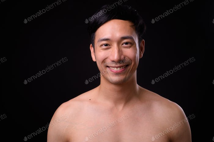 Young handsome Asian man shirtless against black background