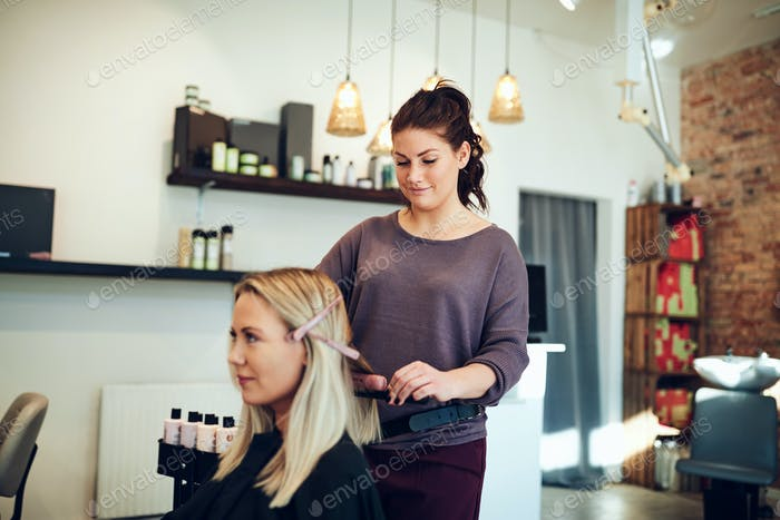 Smiling blonde woman getting her hair straightened at the salon
