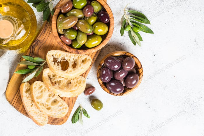 Olives, ciabatta and olive oil on white background