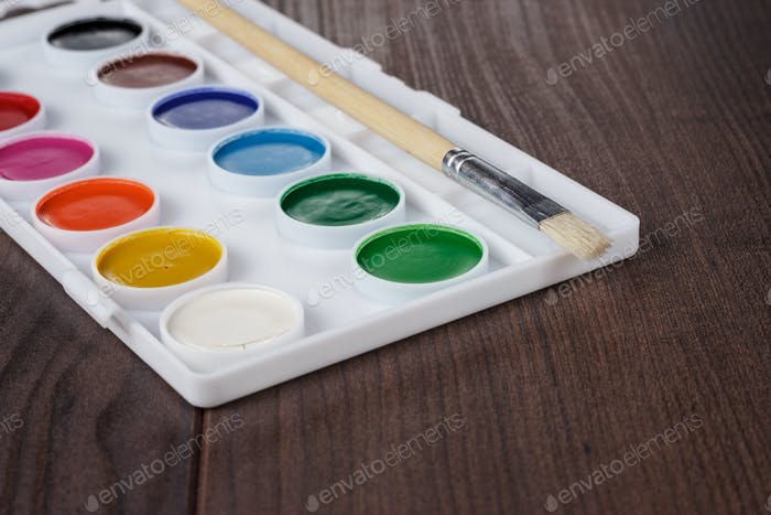 Palette With Paint And Brush On The Table