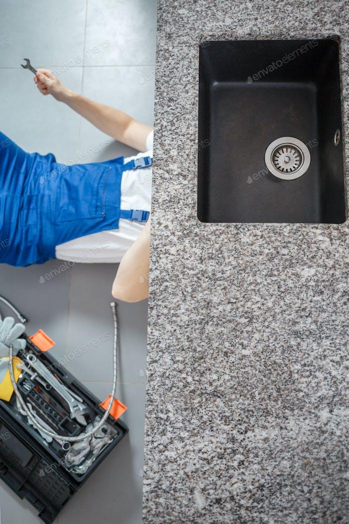 Handyman repairing black sink drain