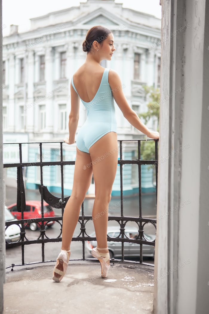 young modern ballet dancer posing on balcony of a house in city