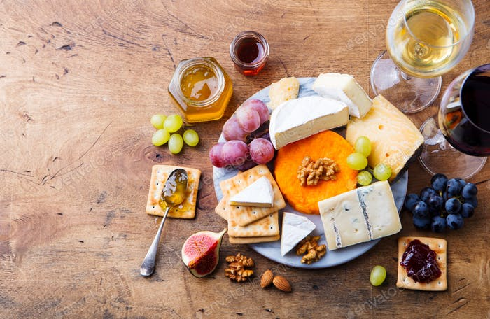 Assortment of Cheese, Grapes with Red and White Wine in Glasses. Wooden Background.