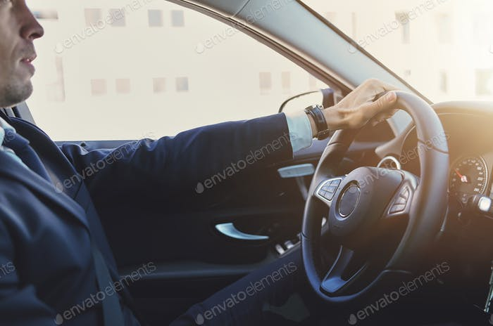 Stylish businessman holding steering wheel and driving