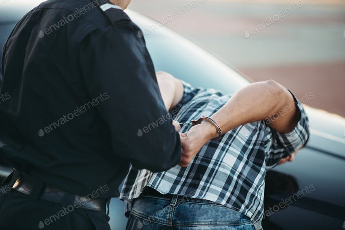Police officer arrests the driver violator on road