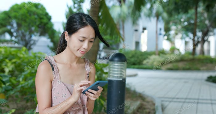 Woman sending sms on cellphone at outdoor park