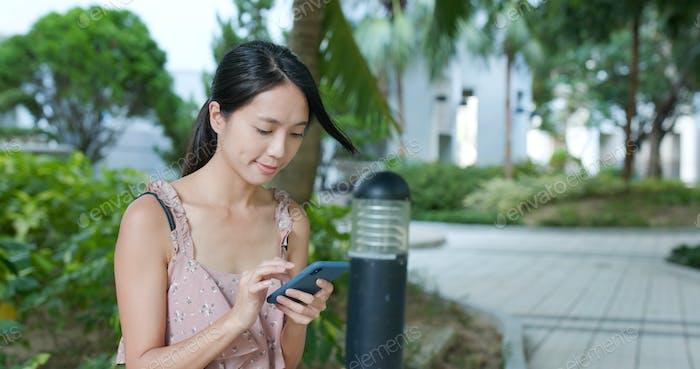 Frau senden SMS auf Handy im Park im Freien