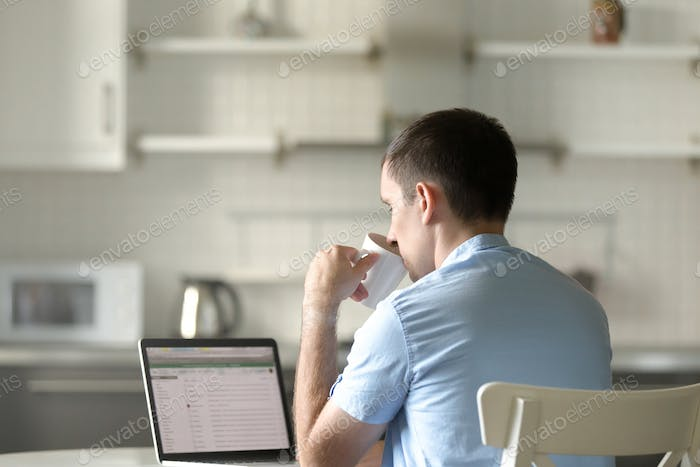 Portrait of a young man at desk with a laptop, drinking