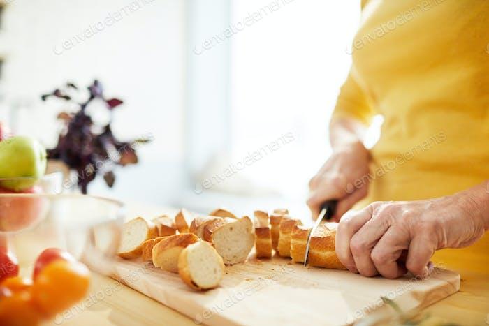 Slicing bread in kitchen