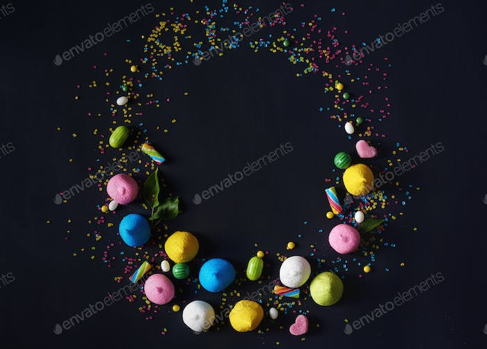 Sprinkled candies on the black background