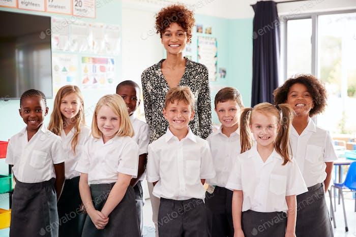 Portrait Of Elementary School Pupils Wearing Uniform Standing In Classroom With Female Teacher