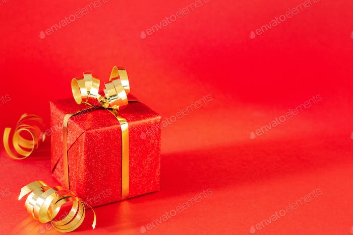 Red Gift Box with Golden Decorations on Red Bacground.