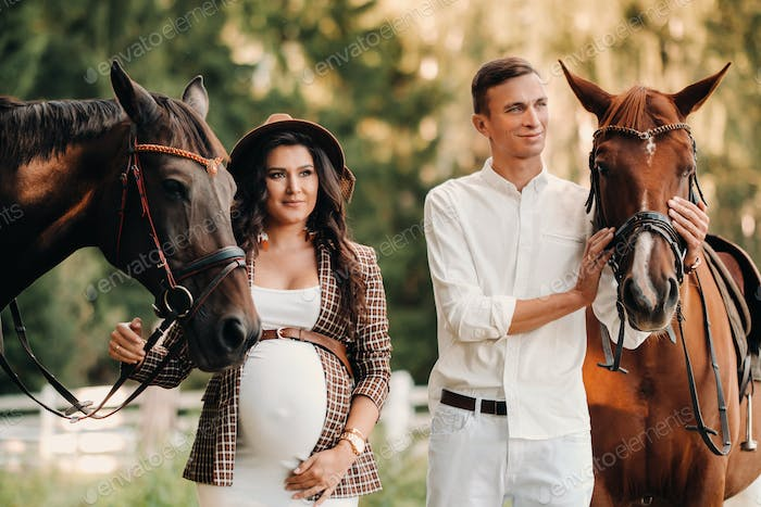 a pregnant girl in a hat and her husband in white clothes stand next to horses in the forest in