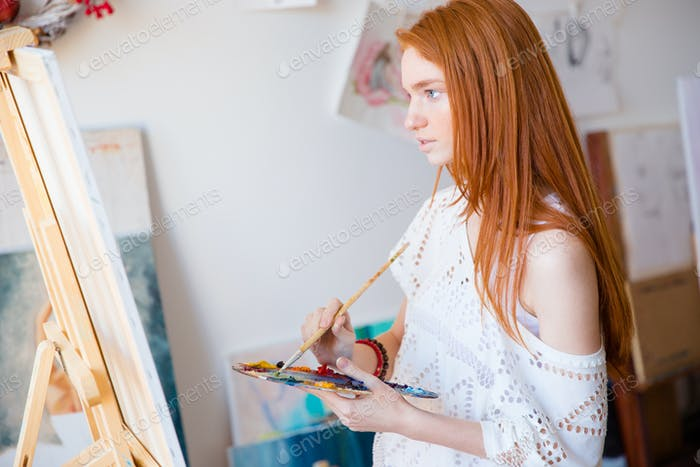 Concentrated pensive woman painter with long hair painting on canvas