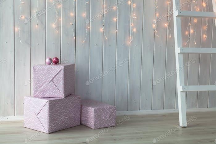 Weihnachtslichter brennen auf weißem Holzhintergrund mit rosa Geschenkboxen und Treppen
