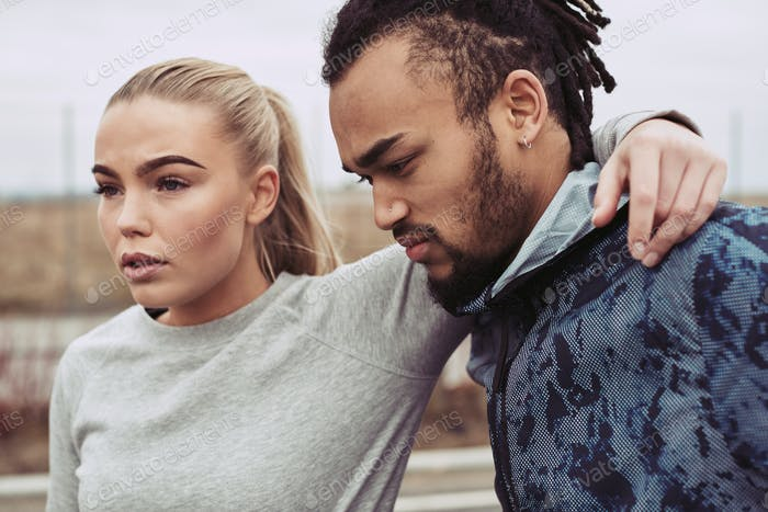 Diverse young couple in sportswear taking a break from jogging