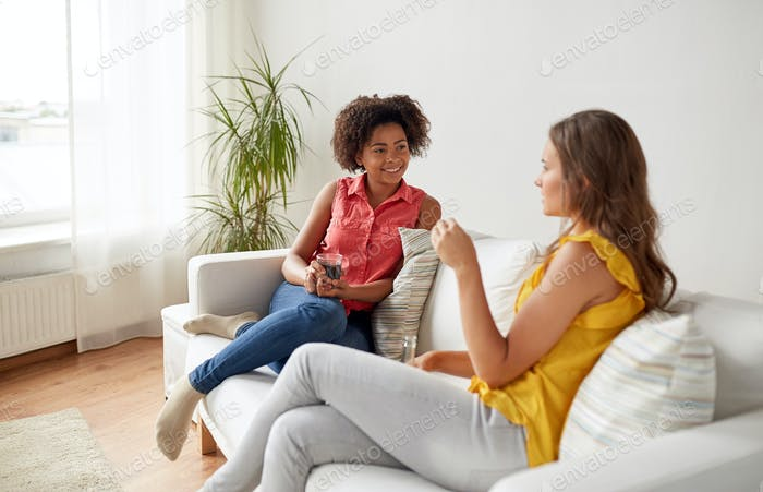 happy women with drink talking gat home