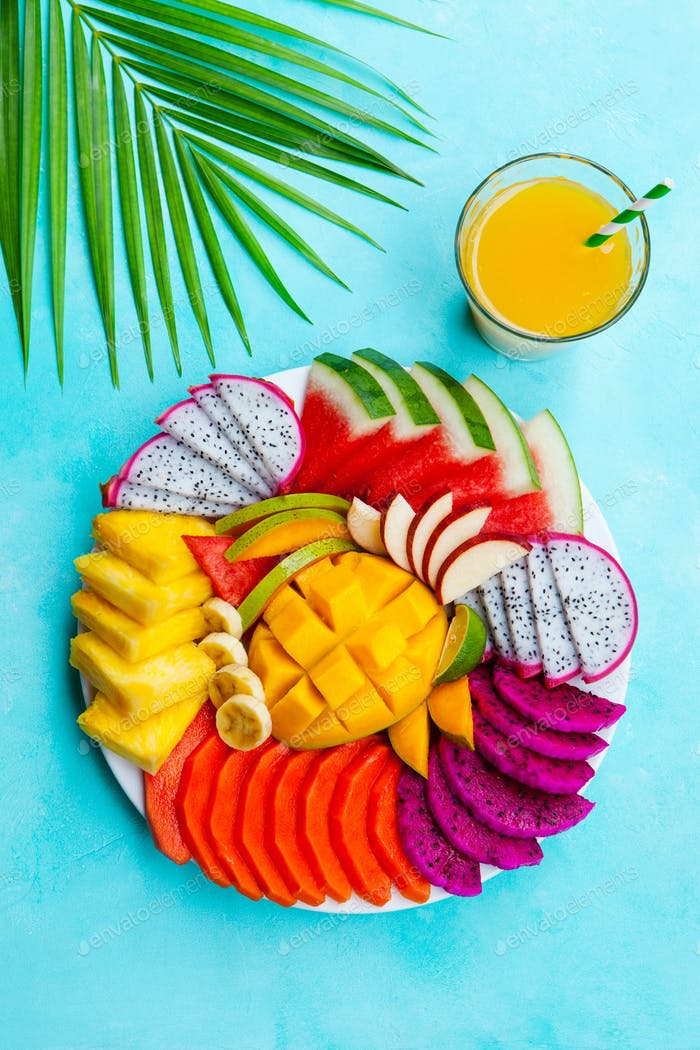 Tropical Fruits Assortment on a White Plate with Mango Smoothie, Juice. Blue Background. Top view.