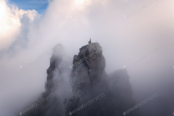 Mountain landscape. High rocks in fog at sunset