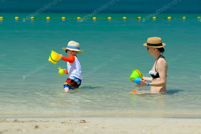 Two year old toddler playing with mother on beach