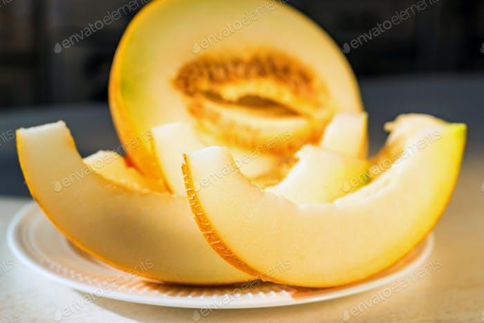 Half melon and melon slices on white plate close