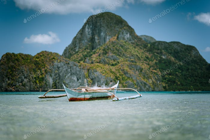 Traditional filippino banca boat in blue tropical lagoon at El Nido bay. Impressive karst mountains