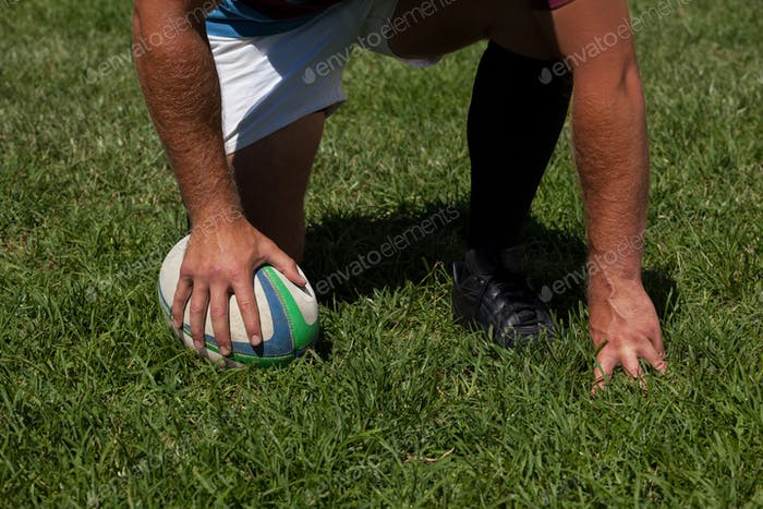 Player crouching with rugby ball on field