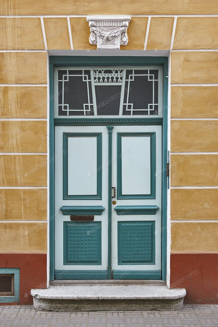 Green old fashioned wooden door on colored facade. Tallinn. Estonia
