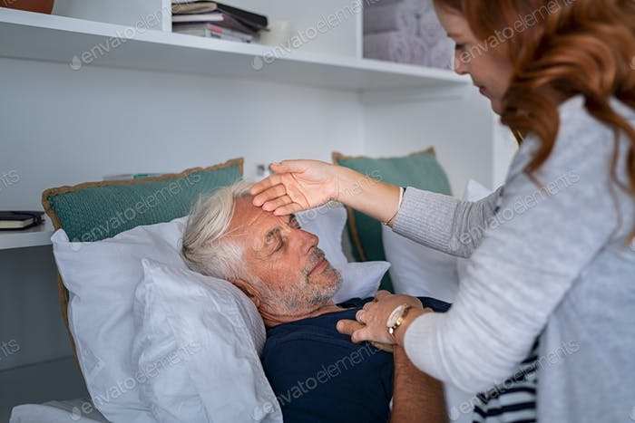 Woman checking man temperature at home