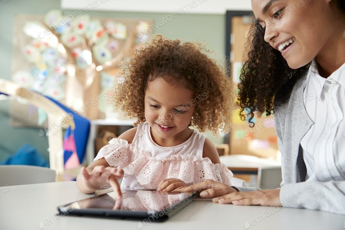Young mixed race schoolgirl using a tablet computer with a female infant school teacher