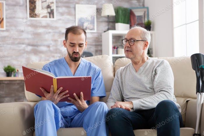 Мужчина врач читает книгу для пожилого возраста мужчины