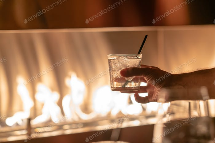 Hand holding a glass of red whine against fire pit