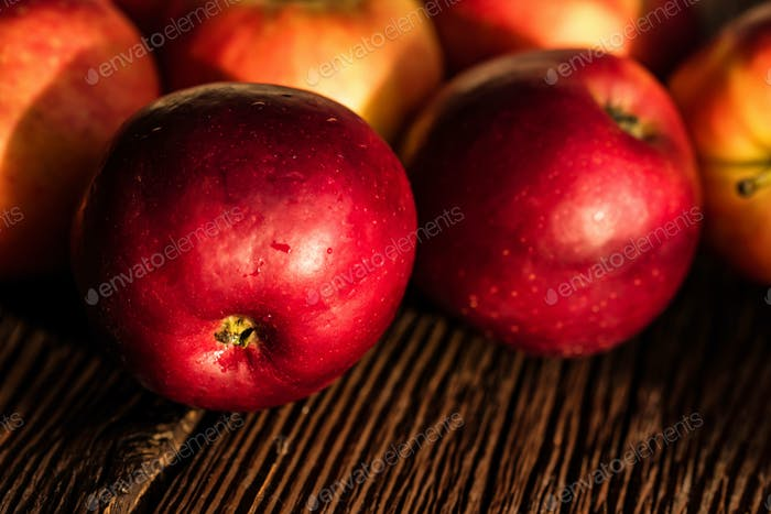 Whole ripe red apples on wooden surface close