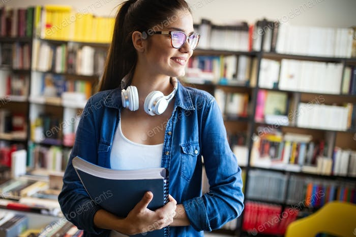 Beautiful student girl learning in a library