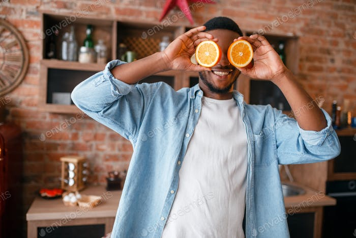 Black man having fun while cooking on the kitchen