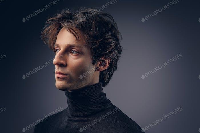 Close-up portrait of a charismatic sensual male in a black sweat