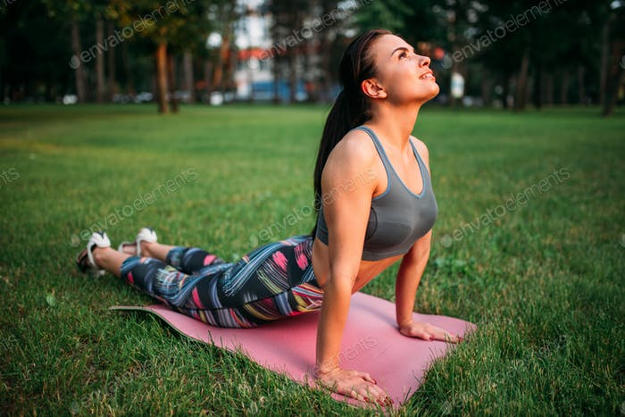 Girl exercise on yoga or fitness mat in park