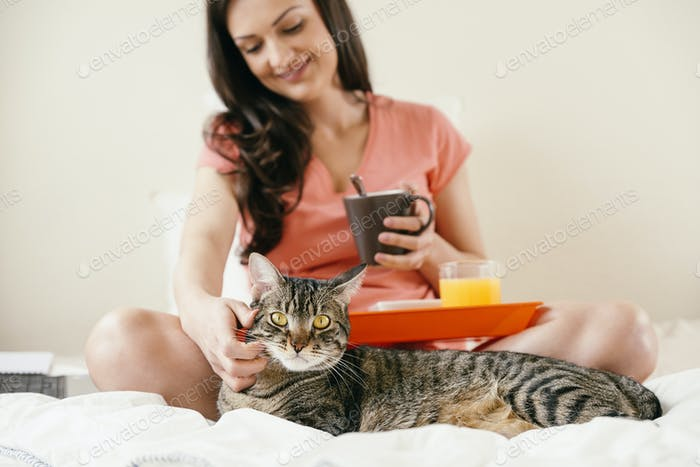 Woman to caress her cat and having breakfast.