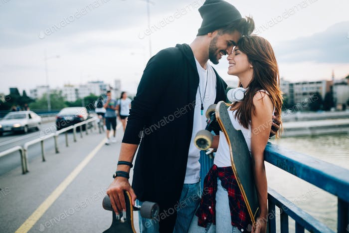 Picture of young attractive couple carrying skateboards