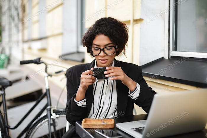 African American girl in glasses sitting at the table of cafe with laptop and holding cup of coffee