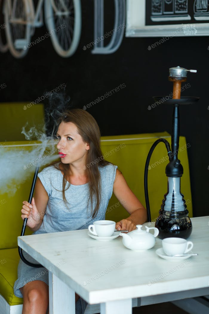 Beautiful woman smoking a hookah and drinking tea in a cafe