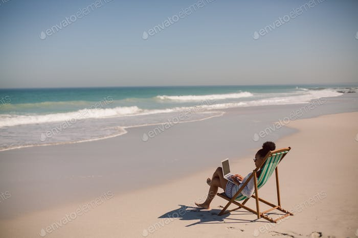 African american woman sitting on beach chair and using laptop at beach