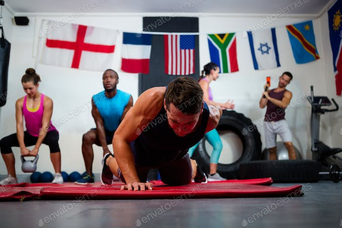 Young male athlete praticing push ups on exercise mat